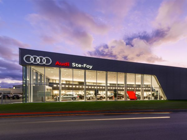 Bâtisse Audi Ste-Foy sous ciel coloré en soirée avec luminaires extérieurs