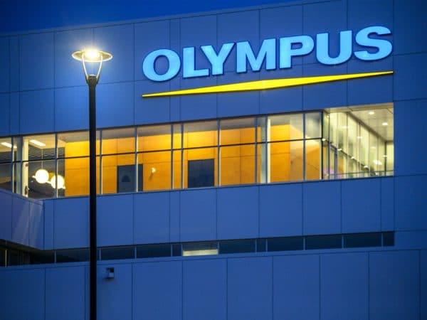Bâtisse Olympus sous ciel de soirée avec luminaires extérieurs