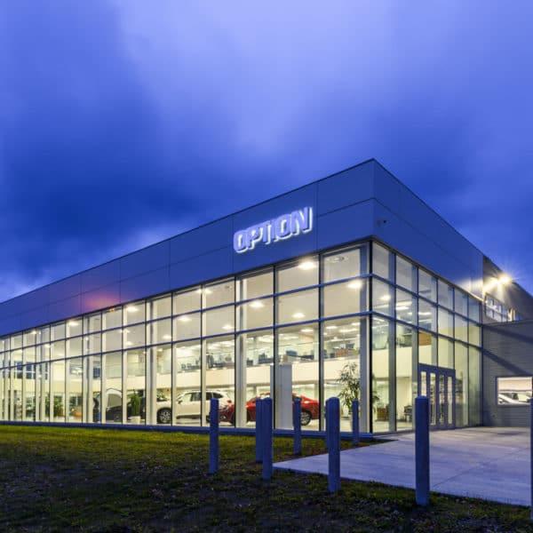 Bâtisse Subaru sous ciel sombre en soirée avec luminaires extérieurs
