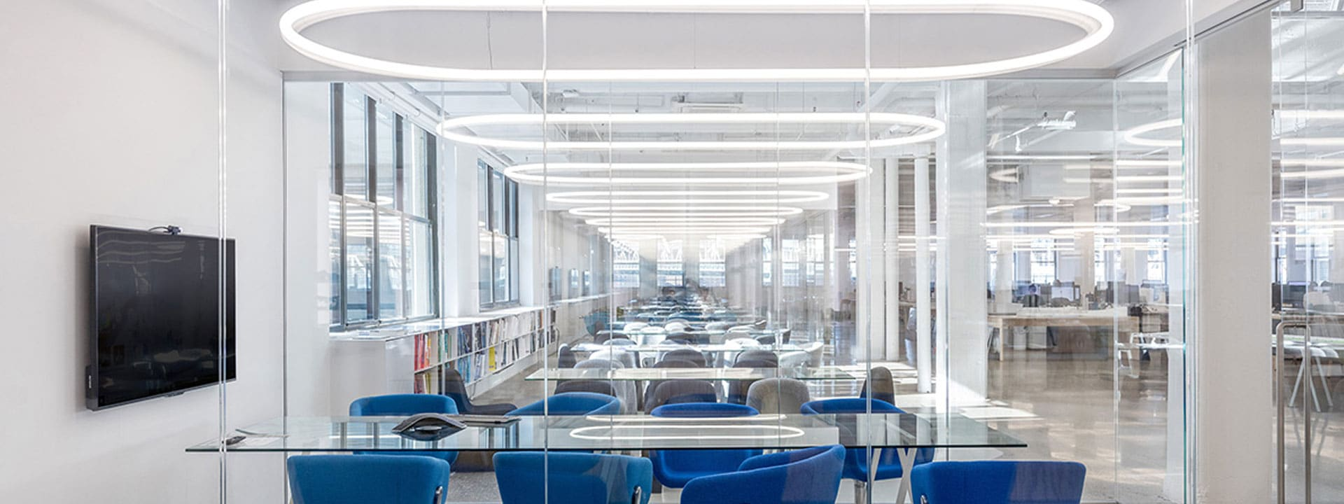 Salles de réunions avec fauteuils bleus et tables en verres, séparées par des vitres transparentes